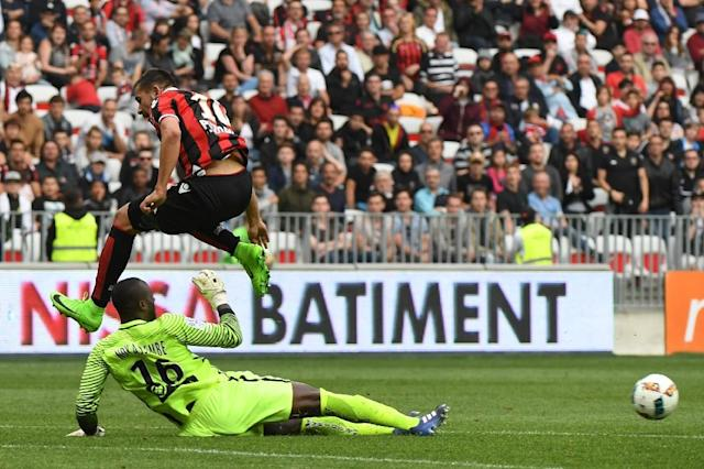 Nice's Mickael Le Bihan (Up) vies with Nancy's goalkeeper Guy-Roland Ndy Assembe at the Allianz Riviera Stadium, in Nice, on April 15, 2017 (AFP Photo/Yann COATSALIOU)