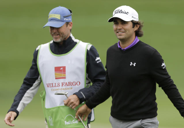 Martin Flores, right, smiles as he walks off the 18th green during the second round of the Wells Fargo Championship golf tournament in Charlotte, N.C., Friday, May 2, 2014. (AP Photo/Chuck Burton)