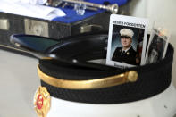 The photos of two firefighters killed at the World Trade Center sit in the hat of Assistant Chief John Pristas of the Cranberry Township Volunteer Fire Company, as he waits to perform taps to mark the 20th anniversary of the 9/11 attacks at Station 21, Saturday, Sept. 11, 2021, in Cranberry, Pa. The company has a permanent memorial, including a piece of steel from the World Trade Center, which gives local residents who can't travel to New York City a place to commemorate the day, according to Jeff Berneberg, a member of the CTVFC. Pristas performed taps six times to mark the four plane crashes and collapse of each of the twin towers. (AP Photo/Rebecca Droke)