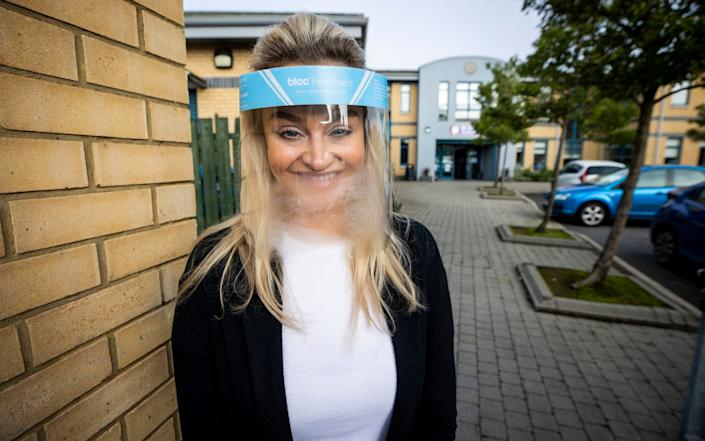 Ashleigh Clarke teacher at St Clare's Primary School in Belfast wearing a protective visor and gloves stands to greet pupils back to school - PA