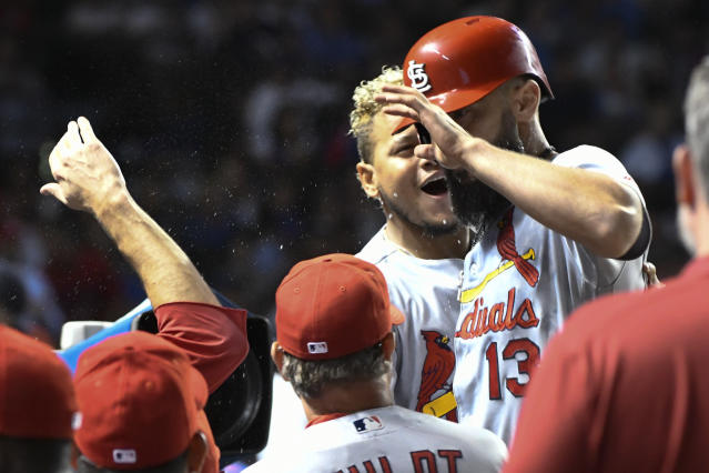 St. Louis Cardinals' Matt Carpenter (13) celebrates in the dugout with relief pitcher Carlos Martinez, back, after he hit a home run against the Chicago Cubs during the tenth inning of a baseball game Thursday, Sept. 19, 2019, in Chicago. (AP Photo/Matt Marton)