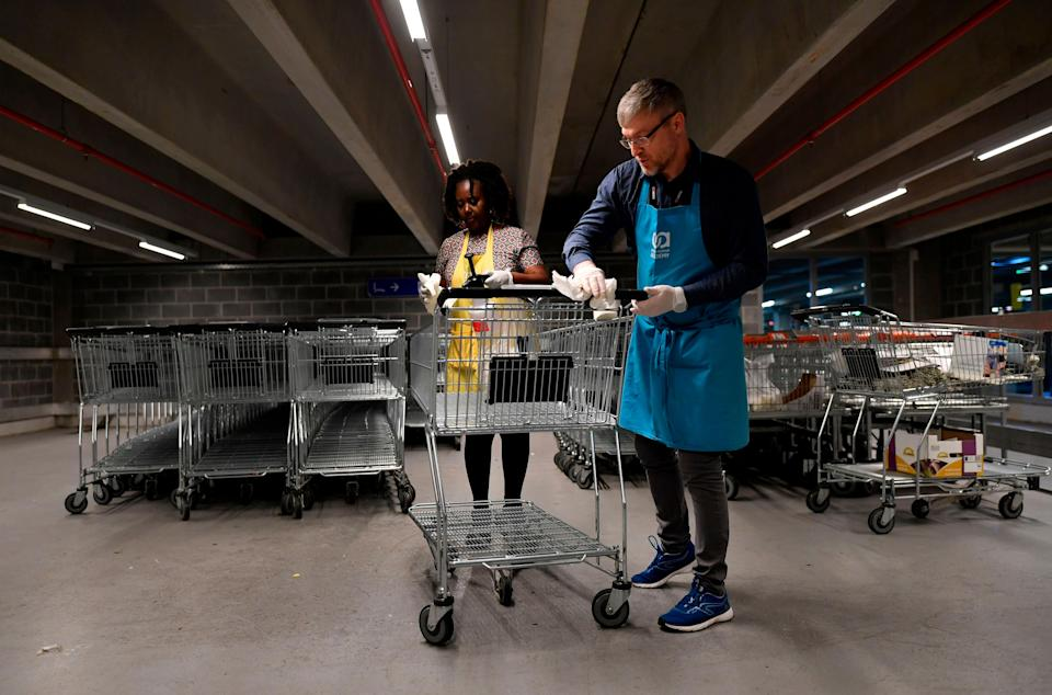 Members of a supermarket in Belgium disinfect a trolley to help stop the spread of the coronavirus. (Photo: JOHN THYS/AFP via Getty Images)