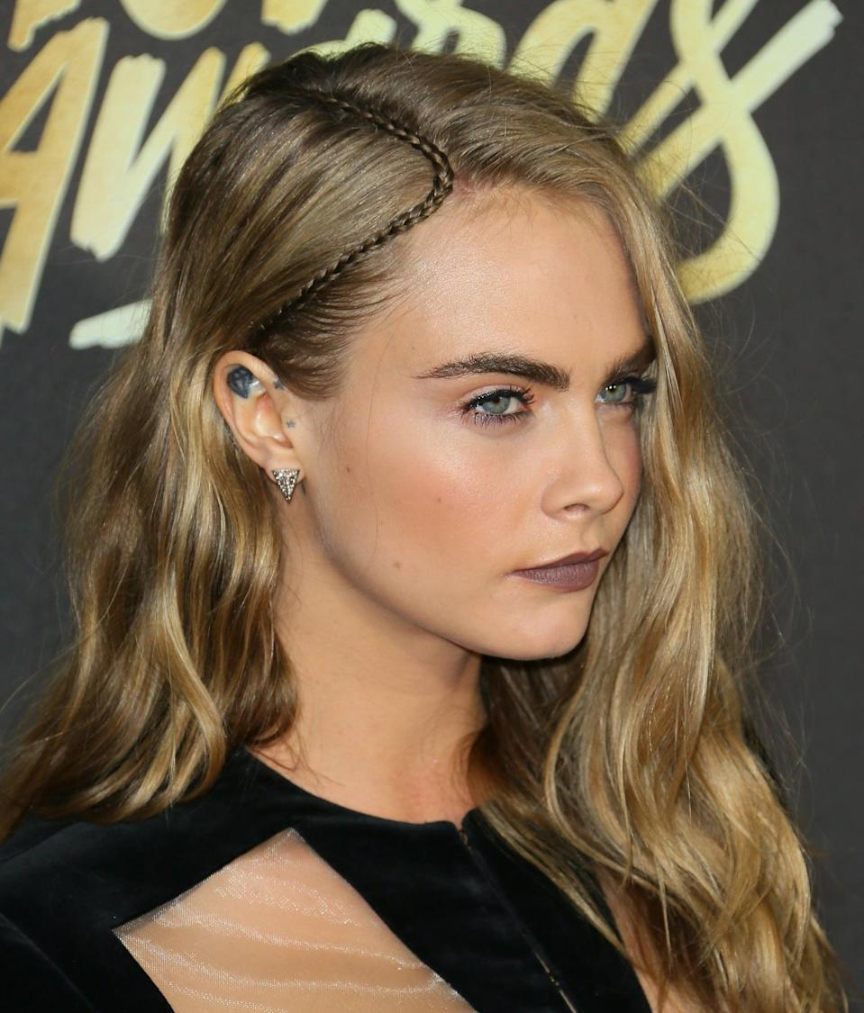 <p>For the 2016 MTV Movie Awards, Roszak found a way to spice up Delevingne's go-to side parting for the casual red carpet event. Taking a piece of hair from behind Delevingne's right ear, Roszak made a tiny plait, braiding it all the way to the ends and tying it off with an elastic. Then she lifted the braid up towards Delevingne's temple, secured it against her hairline with a piece of wig tape, and wrapped it along the part.</p>