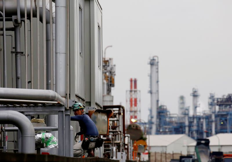 A worker is seen in front of facilities and chimneys of factories at the Keihin Industrial Zone in Kawasaki