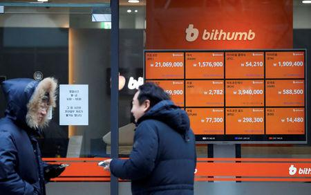 Men talk in front of an electric board showing exchange rates of various cryptocurrencies at Bithumb cryptocurrencies exchange in Seoul, South Korea, January 11, 2018.  REUTERS/Kim Hong-Ji
