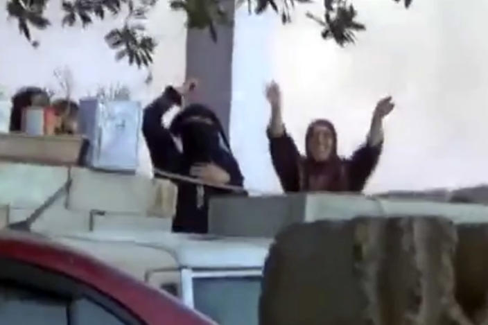In this Thursday March 28, 2013 image taken from video obtained from the Ugarit News, which has been authenticated based on its contents and other AP reporting, shows women celebrating the success of fighters from the Syrian Free Army as they fire on a Syrian army position in Dael less than 15 kilometers (10 miles) from the Jordanian border in Daraa province, Syria. Syrian rebels on Friday captured a strategic town near the border with Jordan after a day of fierce clashes that killed at least 38 people, activists said, as opposition fighters expand their presence in the south, considered a gateway to Damascus. (AP Photo/Ugarit News via AP video)