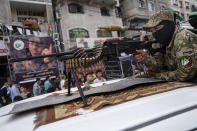 A Hamas militant holds a squad automatic weapon perched atop a truck during a parade through the streets for Bassem Issa, a top Hamas' commander, who was killed by Israeli Defense Force military actions prior to a cease-fire reached after an 11-day war between Gaza's Hamas rulers and Israel, in Gaza City, Saturday, May 22, 2021. (AP Photo/John Minchillo)