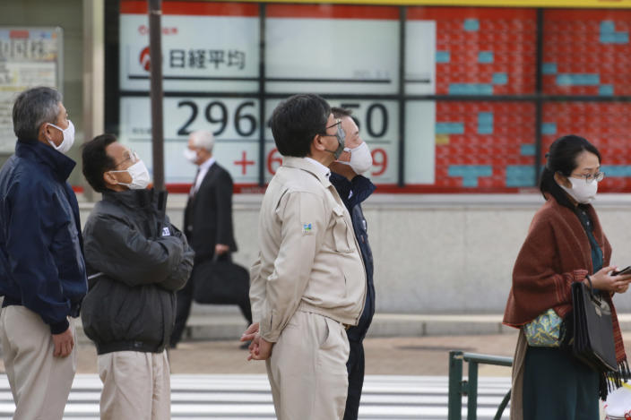 People stand by an electronic stock board of a securities firm in Tokyo, Monday, March 1, 2021. Asian shares were higher on Monday on hopes for President Joe Biden's stimulus package and bargain-hunting buying after the shares' fall last week. (AP Photo/Koji Sasahara)