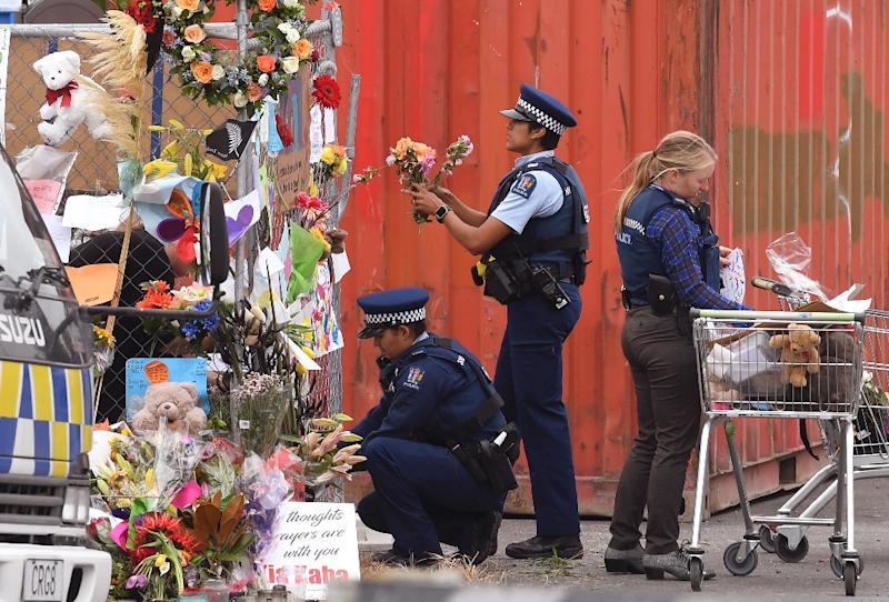 Police place tributes on a memorial wall around the Linwood Mosque in Christchurch (AFP Photo/WILLIAM WEST)