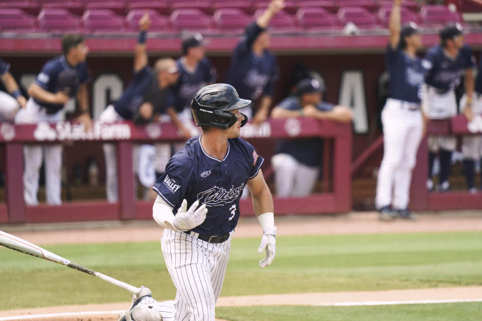 Dallas Baptist's Glenn Jackson watches his home run in the third inning during an NCAA college baseball tournament super regional game against Virginia on Monday, June 14, 2021, in Columbia, S.C. (AP Photo/Sean Rayford)
