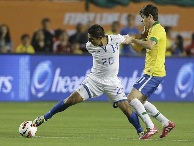 Honduras midfielder Jorge Claros (20) battles for the ball with Brazil midfielder Oscar (11) during the first half of an international friendly soccer game, Saturday, Nov. 16, 2013, in Miami Gardens, Fla. (AP Photo/Wilfredo Lee)
