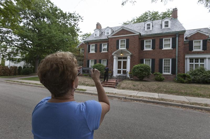 In this photo taken Aug. 12, 2012, Dehlia Jackson of Mechanicsville, Va., photographs Republican Vice Presidential candidate, Rep. Paul Ryan's home in the Courthouse Hill neighborhood in Janesville, Wis. Jackson along with her husband ware driving to Minneapolis and turned off the highway to see Ryan's home. A defining moment for Paul Ryan's hometown came at the height of the Great Recession: General Motors, after nearly a century of making Chevrolets on the banks of the Rock River, shut down its oldest assembly plant and erased 6,000 jobs. A defining question for the campaign Paul Ryan joined this week as the Republican Party's vice presidential nominee just might be what comes next for places like Janesville. (AP Photo/Andy Manis)