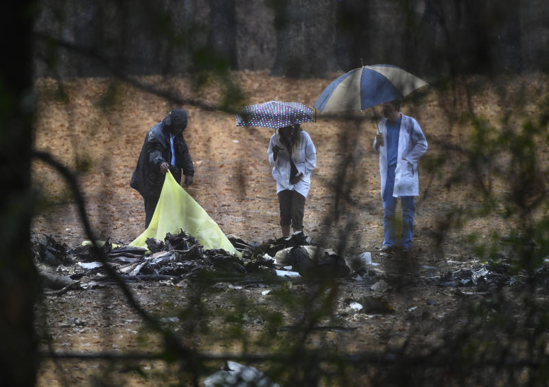 Investigators work the scene of a small plane crash in a city park, Thursday, Dec. 20, 2018, in Atlanta. A few people aboard the business jet were killed when the aircraft plunged into a football field at the park, igniting its fuel and sending thick smoke over a nearby neighborhood Thursday. (AP Photo/John Amis)