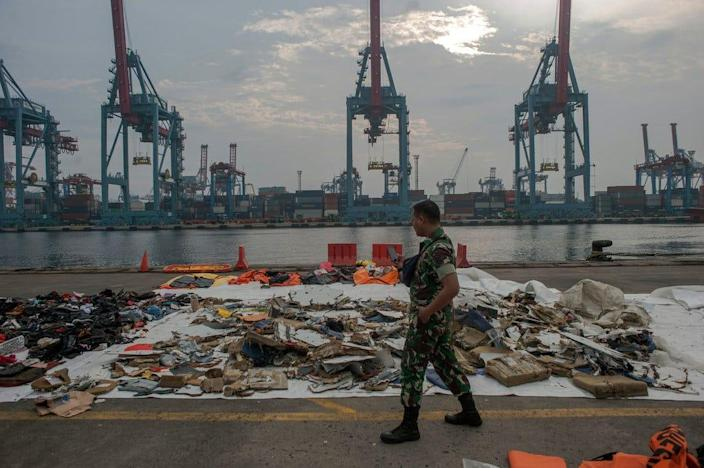 An Indonesian soldier at Tanjung Priok Port in Jakarta walks past debris retrieved from the waters where Lion Air flight JT 610 is believed to have crashed in the Java Sea.