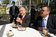 Israeli Prime Minister Benjamin Netanyahu eats a piece of cake as he sits with Jerusalem Mayor, Moshe Leon, at a cafe while Israel further eases coronavirus disease (COVID-19) restrictions in Jerusalem