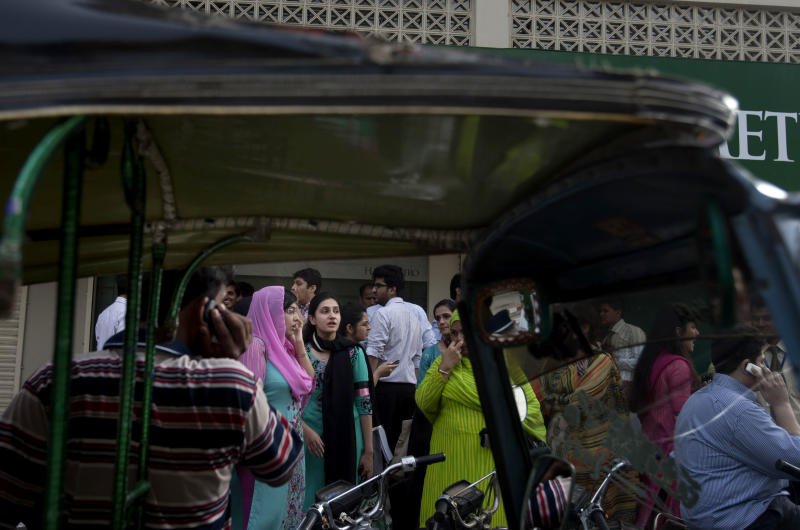 People evacuate buildings and gather on road after a tremor of an earthquake was felt in Karachi, Pakistan, Tuesday, April 16, 2013. A major earthquake described as the strongest to hit Iran in more than half a century flatted homes and offices Tuesday near Iran's border with Pakistan, killing at least tens of people in the sparsely populated region and swaying buildings as far away as New Delhi and the skyscrapers in Dubai and Bahrain. (AP Photo/Shakil Adil)