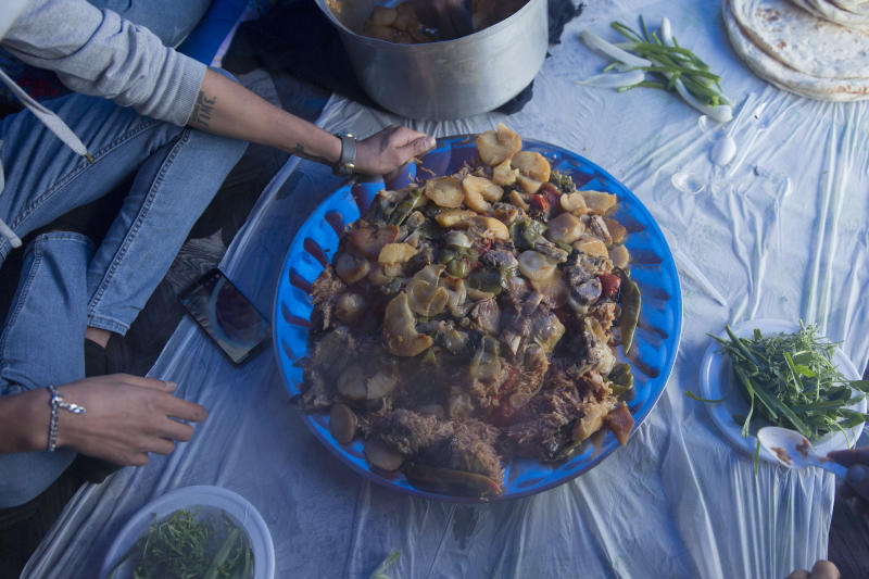 In this photo taken Sunday, Dec. 8, 2019, a volunteer chef serves free meals of the popular dish of Maklouba, a mix of vegetables, meat and rice, to protesters in the center of Baghdad, Iraq.  In Baghdad's Tahrir Square, there are the anti-government protesters demonstrating for a better future for Iraq, and there are the volunteers who feed them. From stuffed lamb and fish, to the giant pots of soups and rice to the plates of lentils and beans, there is no shortage of food to go around. Volunteers from the capital and southern provinces cook traditional dishes that reflect the country's rich cuisine and bring protesters together.  (AP Photo/Nasser Nasser)