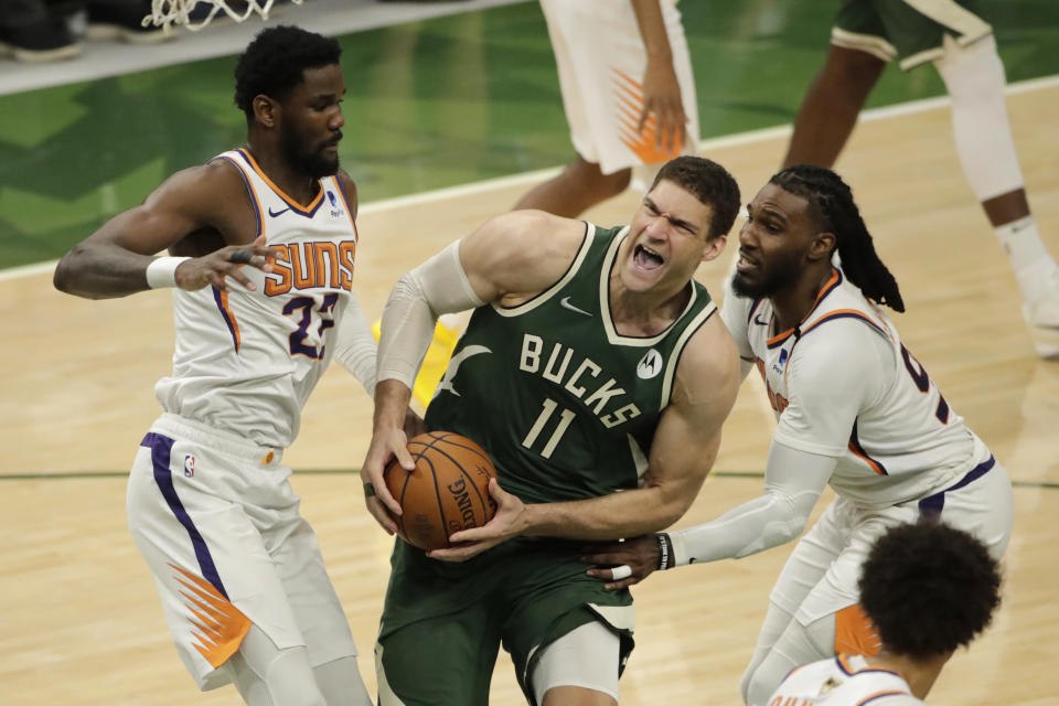 Milwaukee Bucks' Brook Lopez (11) is fouled as he drives between Phoenix Suns' Jae Crowder (99) and Deandre Ayton (22) during the second half of Game 3 of basketball's NBA Finals, Sunday, July 11, 2021, in Milwaukee. (AP Photo/Aaron Gash)