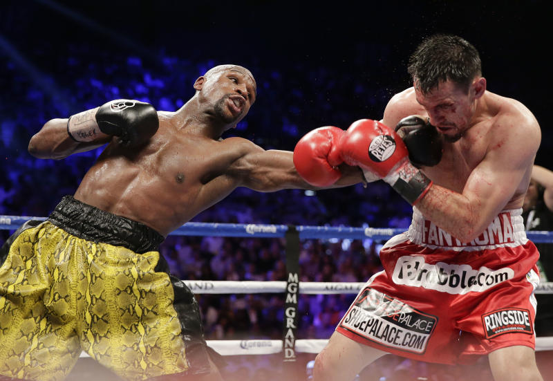Floyd Mayweather Jr., left, throws a left jab at Robert Guerrero in the eighth round during a WBC welterweight title fight, Saturday, May 4, 2013, in Las Vegas. (AP Photo/Isaac Brekken)