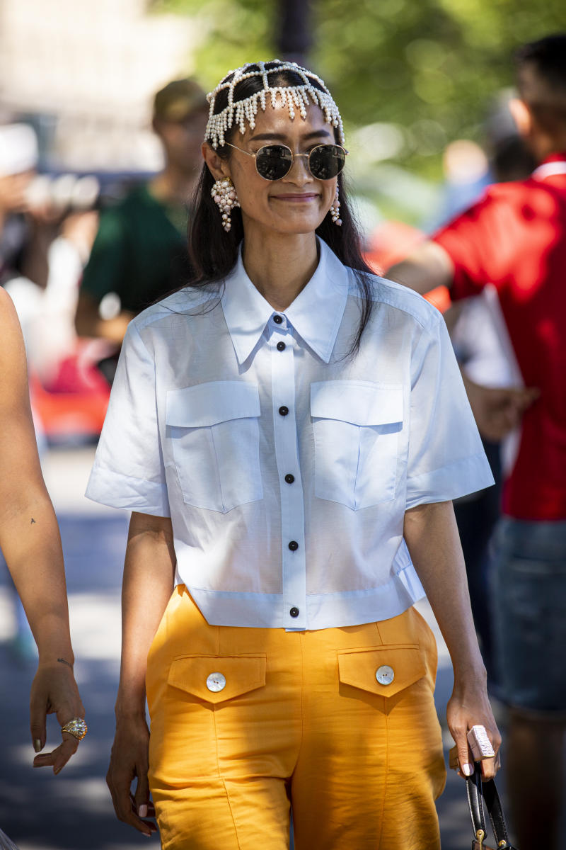 PARIS, FRANCE - JULY 02: A guest, wearing a light blue shirt, orange pants, black bag and pearl hair accessory, is seen outside Alexandre Vauthier show during Paris Fashion Week - Haute Couture Fall/Winter 2019/2020 on July 02, 2019 in Paris, France. (Photo by Claudio Lavenia/Getty Images)