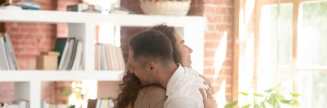 a man and a woman embracing at a support group.