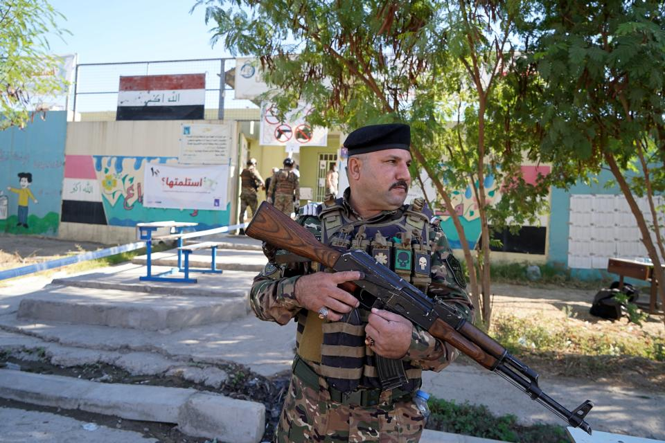 A policeman stands guard outside a polling station during parliamentary elections, in Mosul, Iraq, Sunday, Oct. 10, 2021. Iraq closed its airspace and land border crossings on Sunday as voters headed to the polls to elect a parliament that many hope will deliver much needed reforms after decades of conflict and mismanagement. (AP Photo)