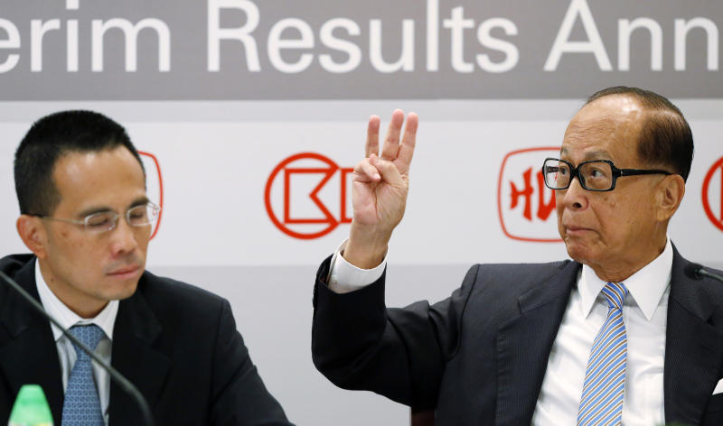 Li Ka-shing, chairman of Hutchison Whampoa Ltd. and Cheung Kong (Holdings) Ltd., right, gestures beside his son, Vice Chairman Victor Li, at the companies' results announcement in Hong Kong, Thursday, Aug. 2, 2012. Hutchison Whampoa said first-half profit tumbled 78 percent from the year before when results were boosted by a big one-time gain. (AP Photo/Kin Cheung)