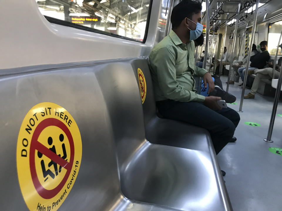 Commuters wearing face masks as a precautionary measure against the coronavirus and travel in a metro train which has markings to ensure social distancing in New Delhi, India, Sunday, Nov. 8, 2020. (AP Photo/Rajesh Kumar Singh)