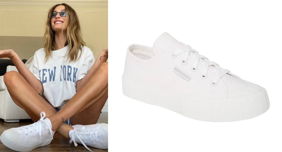 Hailey Bieber with crossed legs posing in white Superga 2630 Cotu sneakers, new york t-shirt, and sunglasses
