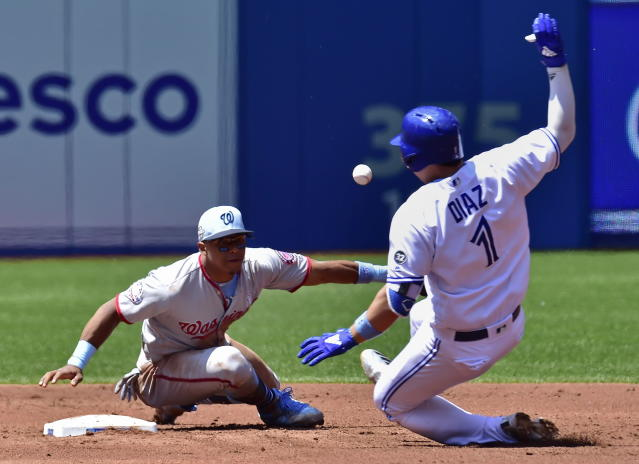 Toronto Blue Jays' Aledmys Diaz, right, slides safely into second base with a double ahead of the tag by Washington Nationals second baseman Wilmer Difo during second-inning baseball game action in Toronto, Sunday, June 17, 2018. (Frank Gunn/The Canadian Press via AP)