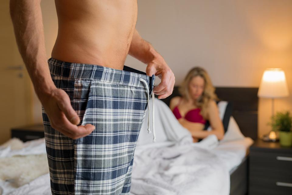 Close-up photo of unrecognizable man having erectile problem in bedroom