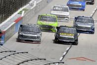 Ben Rhodes, left front, and John Hunter Nemechek, right front, lead the field into Turn 1 during a NASCAR Truck Series auto race at Texas Motor Speedway in Fort Worth, Texas, Saturday, June 12, 2021. (AP Photo/Larry Papke)