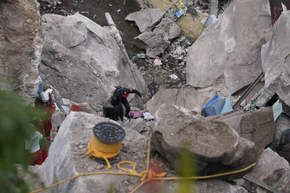 Firefighters scale a three-story pile of rocks in Tlalnepantla, on the outskirts of Mexico City, when a mountain gave way on Friday, Sept. 10, 2021, plunging rocks the size of small homes onto a densely populated neighborhood. (AP Photo/Eduardo Verdugo)