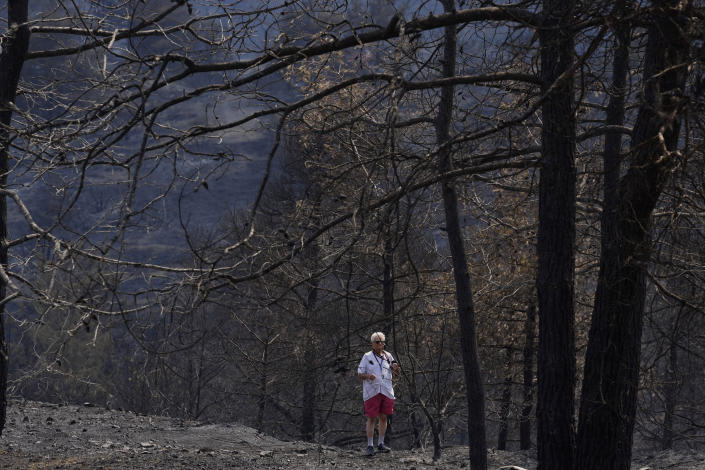 """A man walks through the burned forest, in Ora village, in the Larnaca mountain region, Cyprus, Sunday, July 4, 2021. Cyprus' interior minister says four people have died in what he called the """"most destructive"""" fire in the island nation's history. (AP Photo/Petros Karadjias)"""