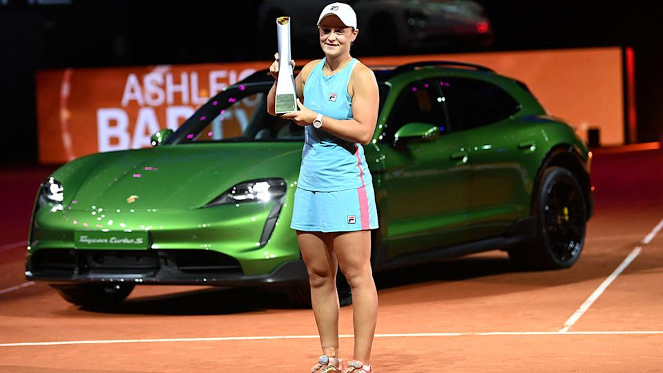 Ash Barty, pictured here with the trophy and her new Porsche Taycan Turbo S Cross Turismo.