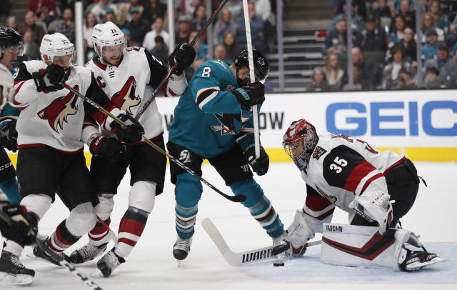 San Jose Sharks' Joe Pavelski (8) battles for the puck against Arizona Coyotes' Darcy Kuemper (35), Alex Goligoski (33) and Oliver Ekman-Larsson (23) in the second period of an NHL hockey game in San Jose, Calif., Sunday, Dec. 23, 2018. (AP Photo/Josie Lepe)