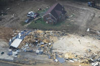 FILE — In this Aug. 25, 2021, file photo, debris from damaged buildings is strewn about after an Aug. 21 flood in Waverly, Tenn. After the devastating flood, the town of just over 4,000 people faces a dilemma. More than 500 homes and 50 businesses were damaged. That will likely result in massive revenue losses while the city spends millions on cleanup and repairs. If those homes and businesses don't return, the town could die a lingering death. But if they build back along the creek, they could be risking another disaster. (AP Photo/Mark Humphrey)