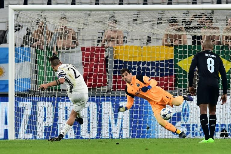 Juventus' forward Paulo Dybala (L) scores a penalty against Porto's goalkeeper Iker Casillas during their UEFA Champions League match on March 14, 2017 in Turin