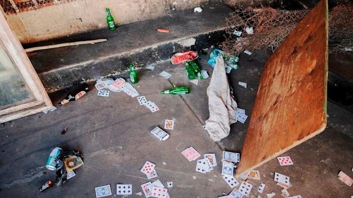 Cards and beer bottles lie on the floor following a security force raid in a Johannesburg suburb