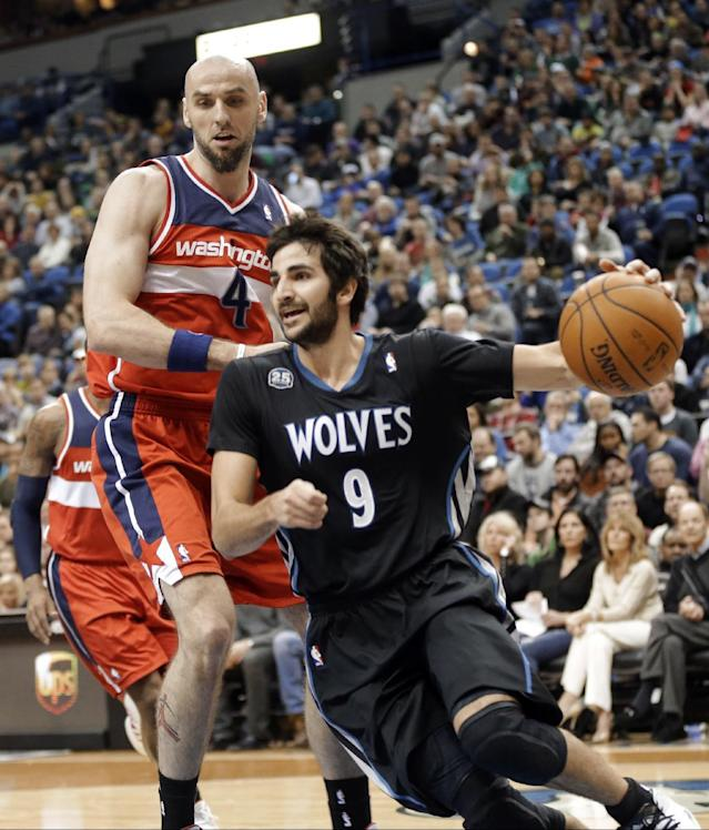 Minnesota Timberwolves' Ricky Rubio, right, drives around Washington Wizards' Marcin Gortat during the first quarter of an NBA basketball game, Friday, Dec. 27, 2013, in Minneapolis. (AP Photo/Jim Mone)