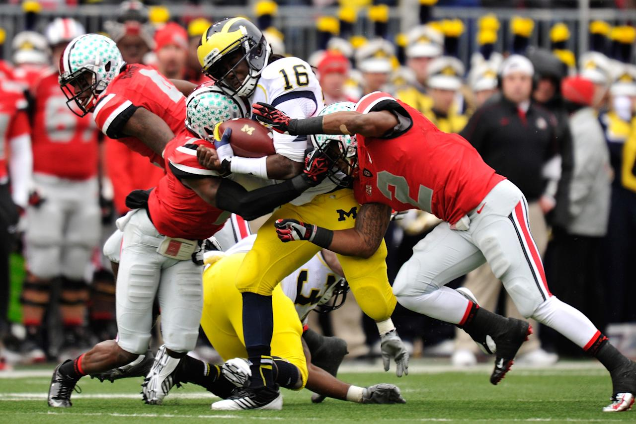 COLUMBUS, OH - NOVEMBER 24:  Denard Robinson #16 of the Michigan Wolverines breaks through the tackle attempts by Travis Howard #7 of the Ohio State Buckeyes and Christian Bryant #2 of the Ohio State Buckeyes in the first half on his way to a 67-yard touchdown run at Ohio Stadium on November 24, 2012 in Columbus, Ohio.  (Photo by Jamie Sabau/Getty Images)