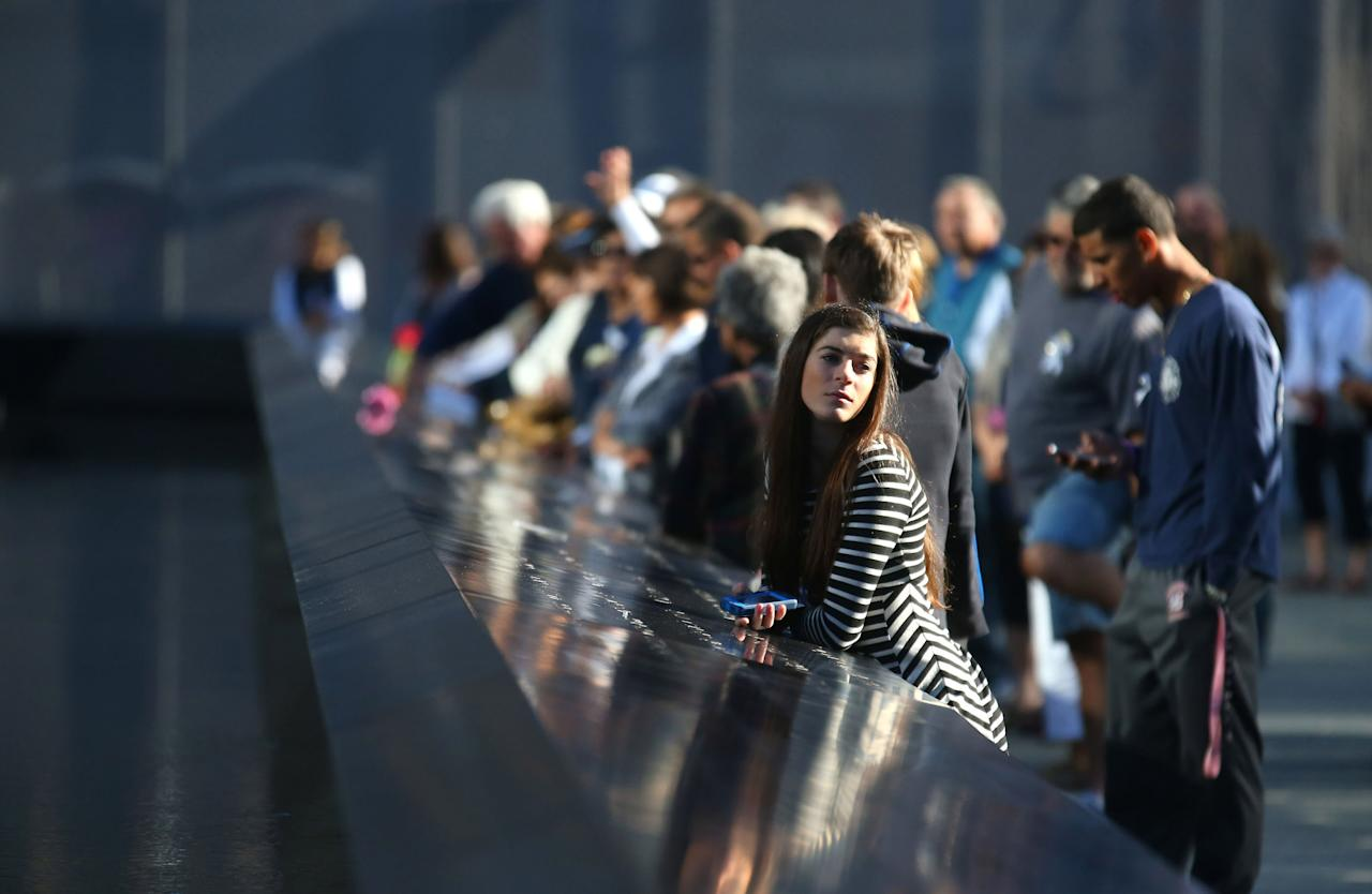 NEW YORK - SEPTEMBER 11:  People stand during a moment of silence at 8:46 AM for the observance of time American Airline Flight 11 struck north World TradeTower during memorial ceremonies for the eleventh anniversary of the terrorist attacks on lower Manhattan at the World Trade Center site September 11, 2012 in New York City. New York City and the nation are commemorating the eleventh anniversary of the September 11, 2001 attacks which resulted in the deaths of nearly 3,000 people after two hijacked planes crashed into the World Trade Center, one into the Pentagon in Arlington, Virginia and one crash landed in Shanksville, Pennsylvania. (Photo by Chang W. Lee-Pool/Getty Images)