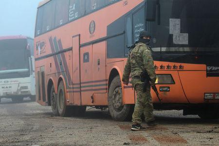 A rebel fighter stands near buses carrying people evacuated from the two villages of Kefraya and al-Foua, after an agreement reached between rebels and Syria's army, at insurgent-held al-Rashideen