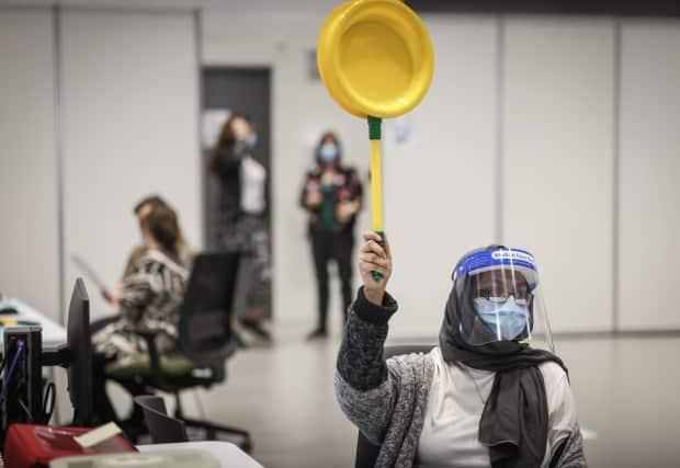 A nurse holds a panel signaling for the next vaccine client at the Telus Convention Centre immunization site in Calgary on April 20. (Alberta Health Services - image credit)