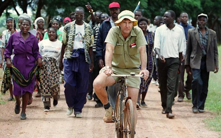 Zimbabwean commercial farmer Tommy Bayley rides an old bicycle ahead of war veterans and villagers who invaded his farm Danbury Park, 30 kilometres (18.6 miles) northwest of Harare, to an abandoned house to use as temporary shelter April 8, 2000. Zimbabwe was thrown into turmoil in February when Robert Mugabe's supporters and self-styled veterans of the 1970s war of liberation invaded white-owned farms, demanding land they said had been illegally taken away by colonisers. - Howard Burditt/REUTERS