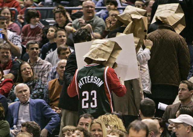 Former Milwaukee Bucks owner Herb Kohl, left, watches as fans with bags on their heads are led out of the arena in 2008. (AP)