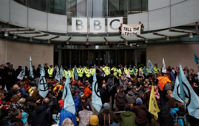 Protesters hold a banner next to the BBC logo at the company's headquarters during an Extinction Rebellion demonstration in London, Britain October 11, 2019. REUTERS/Peter Nicholls