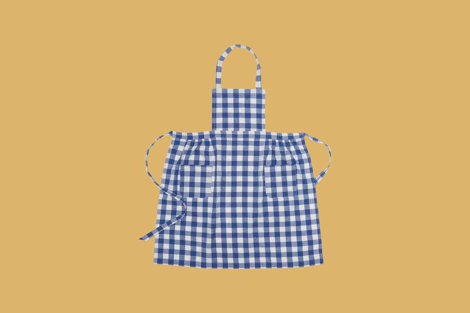 """<p>A little gingham goes a long way on an apron. This colorful option is handwoven by artisans in Chiapas, Mexico, and features two front pockets for sticking utensils, towels, and other <a href=""""https://www.marthastewart.com/shop/martha-exclusives/martha-stewart-kitchen-essentials-sc281474979922971.html"""" rel=""""nofollow noopener"""" target=""""_blank"""" data-ylk=""""slk:cooking-related stuff"""" class=""""link rapid-noclick-resp"""">cooking-related stuff</a>.</p> <p><strong><em>Shop Now: </em></strong><em>Heather Taylor Home Gingham Denim Apron, $98, </em><a href=""""https://heathertaylorhome.com/shop/gingham-denim-apron/"""" rel=""""nofollow noopener"""" target=""""_blank"""" data-ylk=""""slk:heathertaylorhome.com"""" class=""""link rapid-noclick-resp""""><em>heathertaylorhome.com</em></a><em>.</em></p>"""