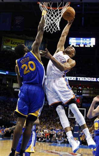 Oklahoma City Thunder guard Russell Westbrook, right, shoots in front of Golden State Warriors forward Ekpe Udoh (20) in the first quarter of an NBA basketball game in Oklahoma City, Friday, Feb. 17, 2012. (AP Photo/Sue Ogrocki)