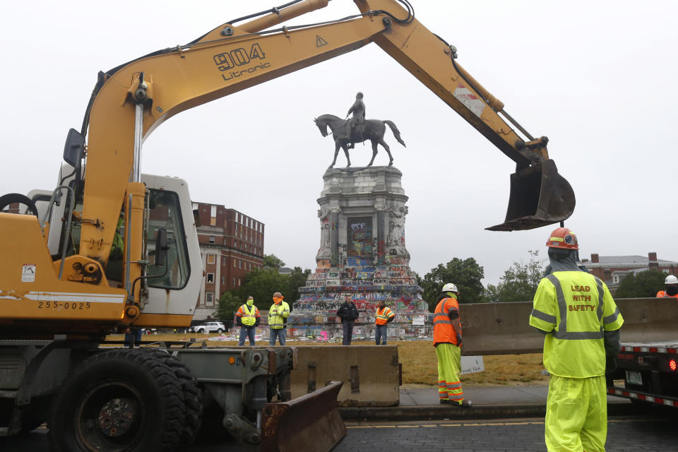 Workers for The Virginia Department of General Services install concrete barriers around the statue of Confederate General Robert E. Lee on Monument Avenue Wednesday June 17, 2020, in Richmond, Va. The barriers are intended to protect the safety of demonstrators as well as the structure itself. (AP Photo/Steve Helber)